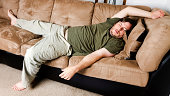 Lazy guy flung all over the couch