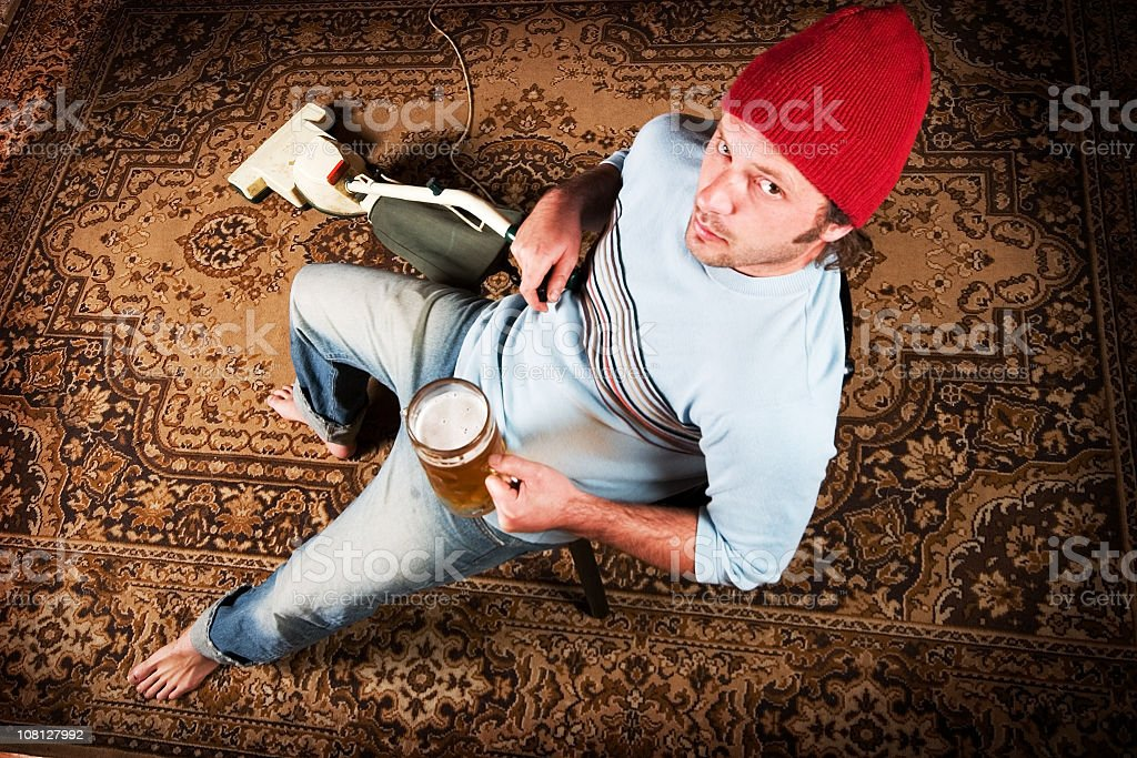 Lazy Man Vacuuming and Drinking Beer royalty-free stock photo