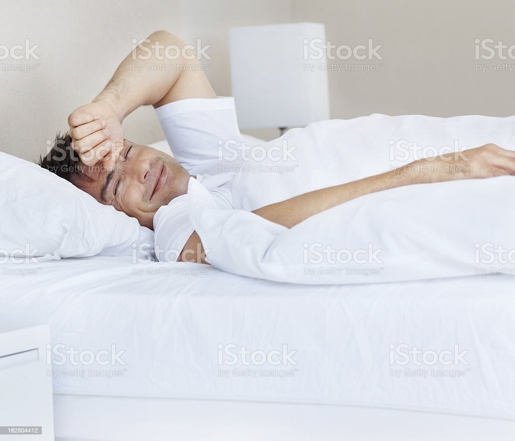 Lazy mature man lying in bed at home royalty-free stock photo