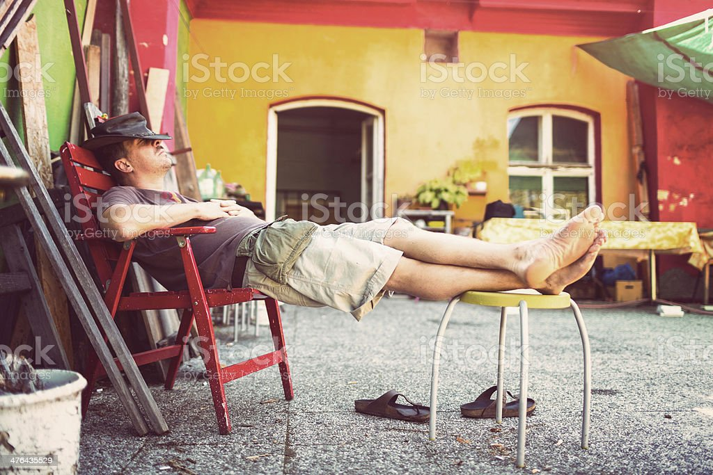 Lazy mid adult man sleeping on terrace during the day royalty-free stock photo