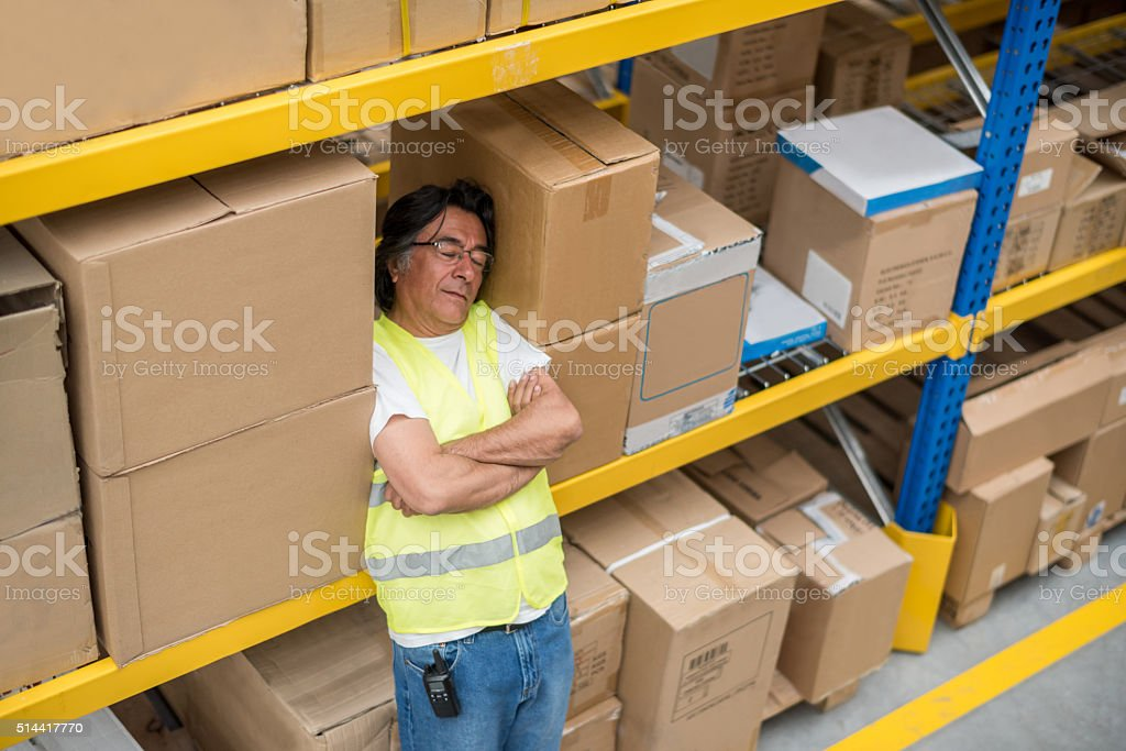 Lazy worker sleeping at a warehouse stock photo