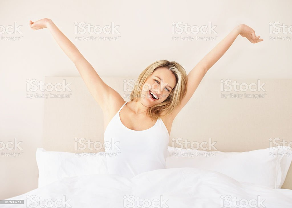 Lazy young lady stretching hands on bed royalty-free stock photo
