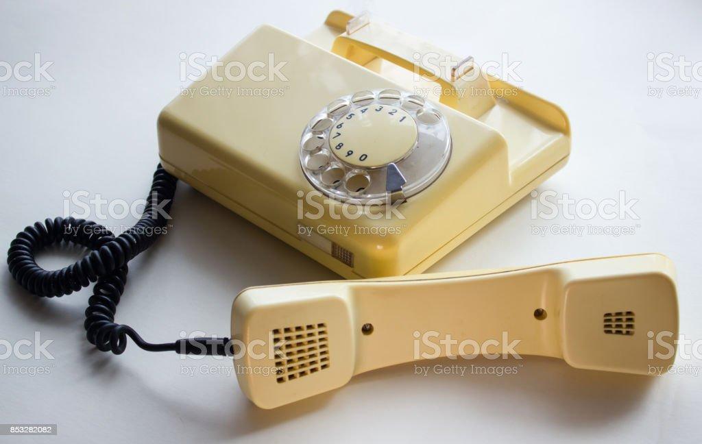 Оld yellow phone with the handset 0ff stock photo