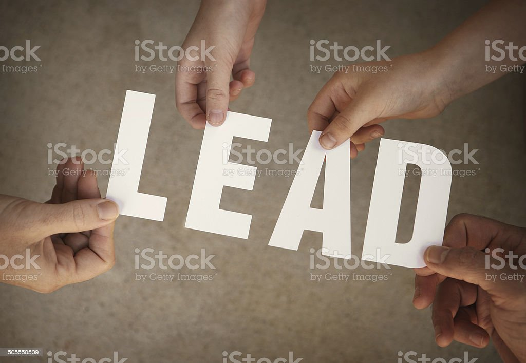 Lead - Hands Holding White Letters Over Grunge Background stock photo