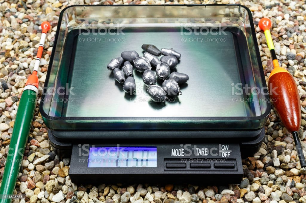 Lead weights for fishing floats on a pocket scale stock photo