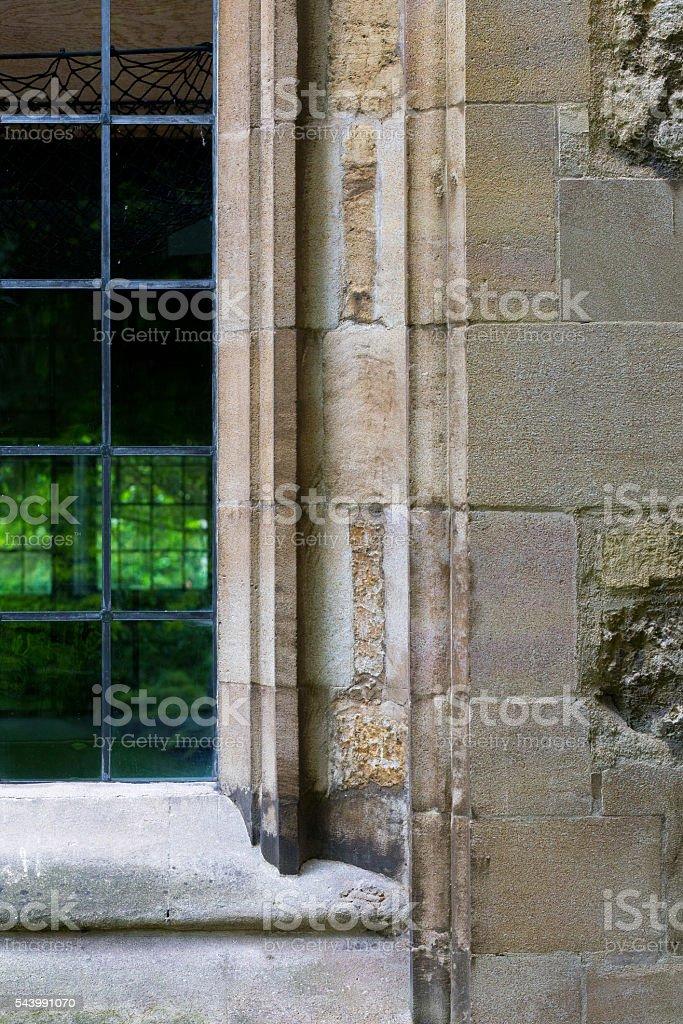 Leaded glass window in limestone wall stock photo