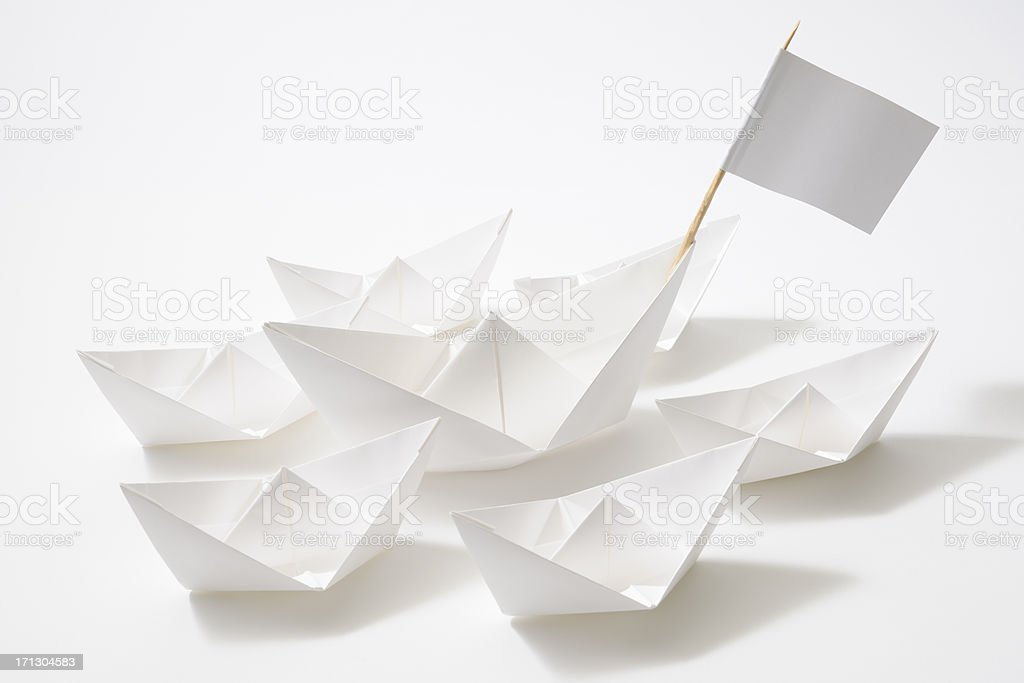 Leader ship of white paper boats fleet on white background royalty-free stock photo