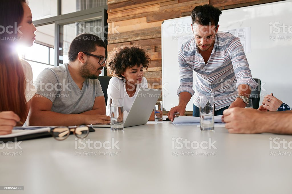 Leader showing business plan to colleagues during a meeting stock photo
