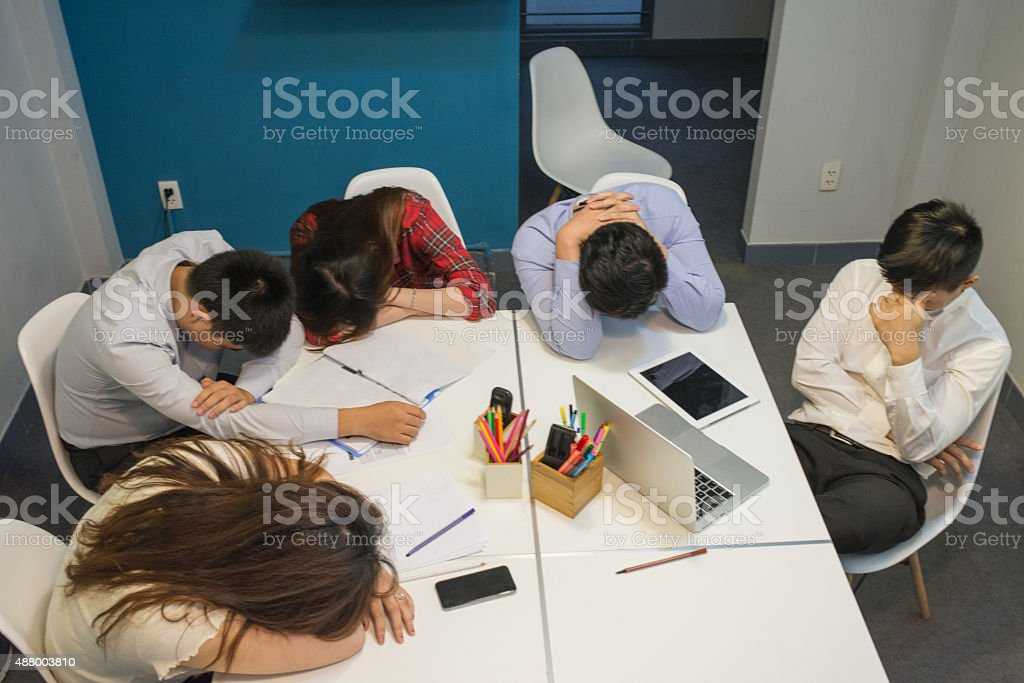 Leader thinking about the solution while his team members sleeping stock photo