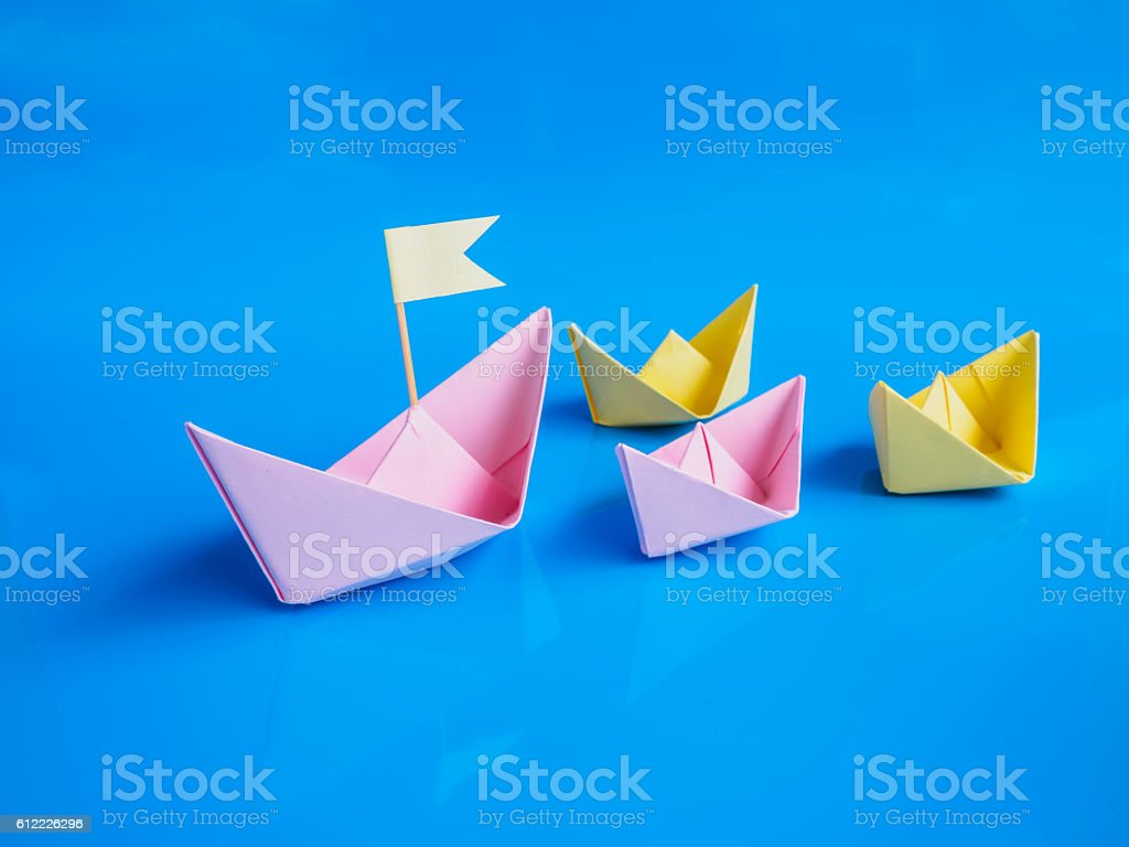 Leadership and team work concept, Craft of paper boat group stock photo