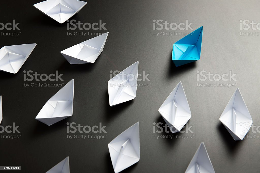 Leadership concept illustrated with paper ships stock photo