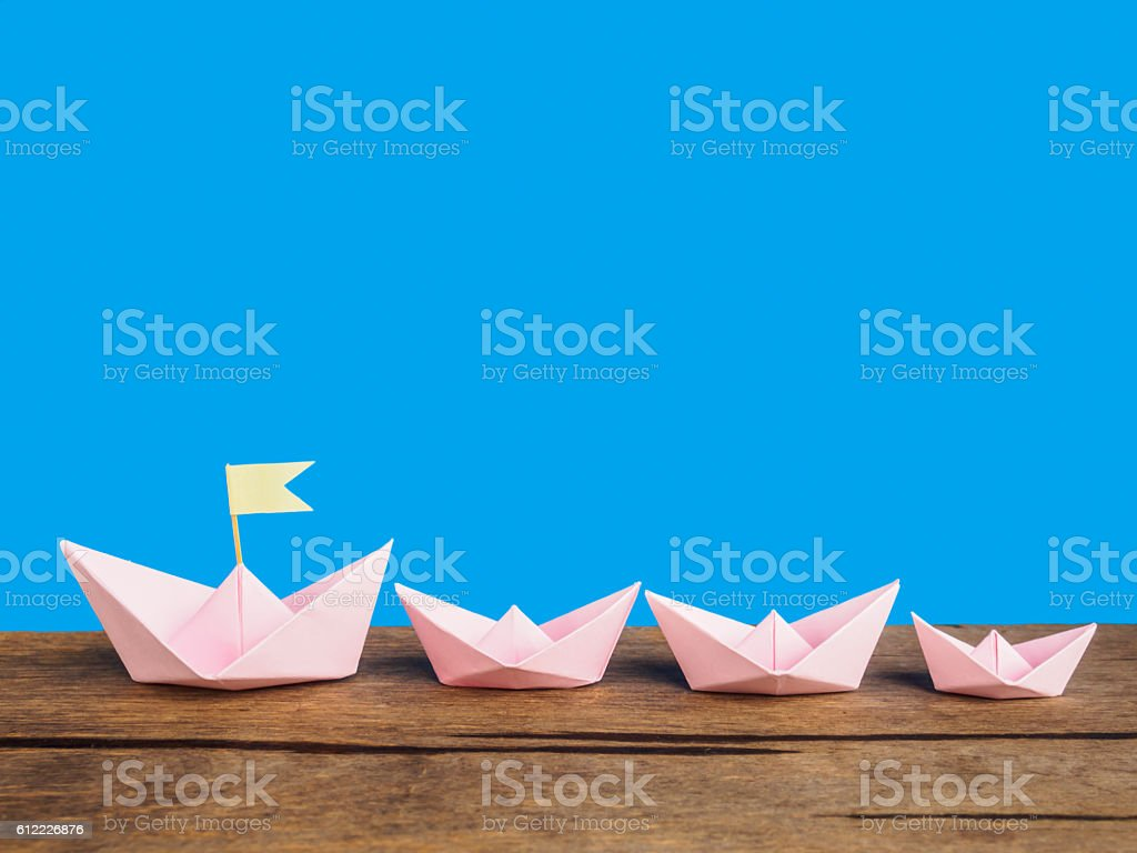 Leadership concept, Pink paper boat group (Origami) stock photo