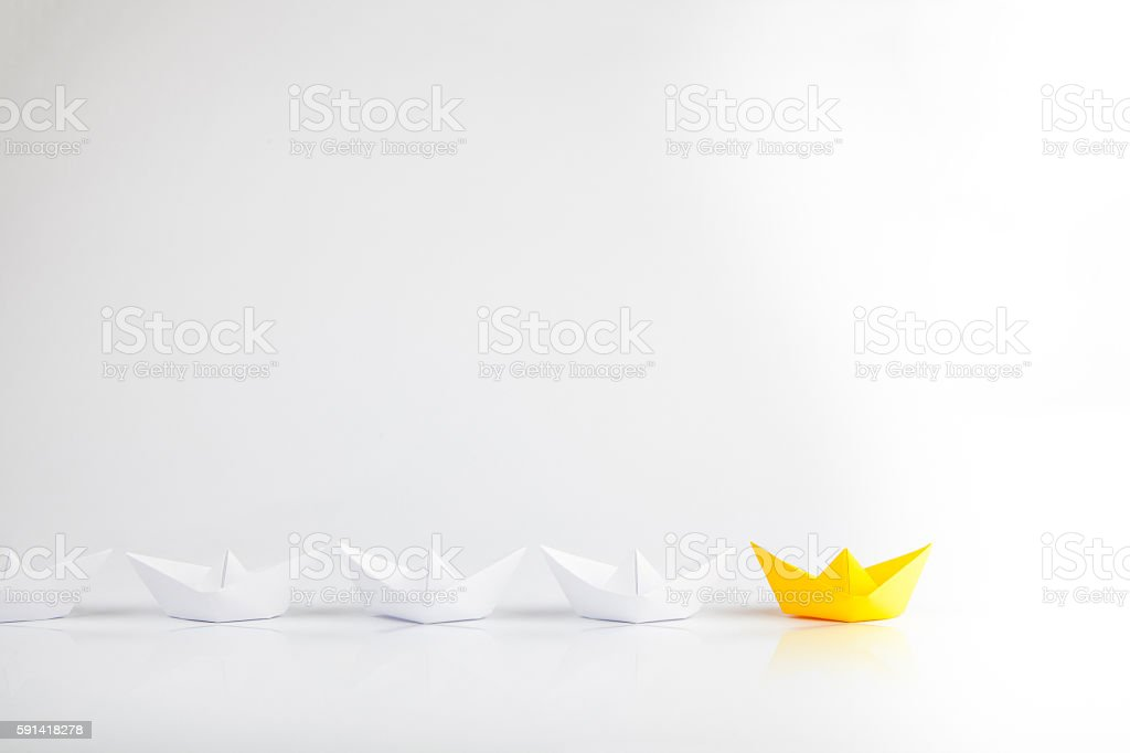 Leadership concept using yellow paper ship among white stock photo
