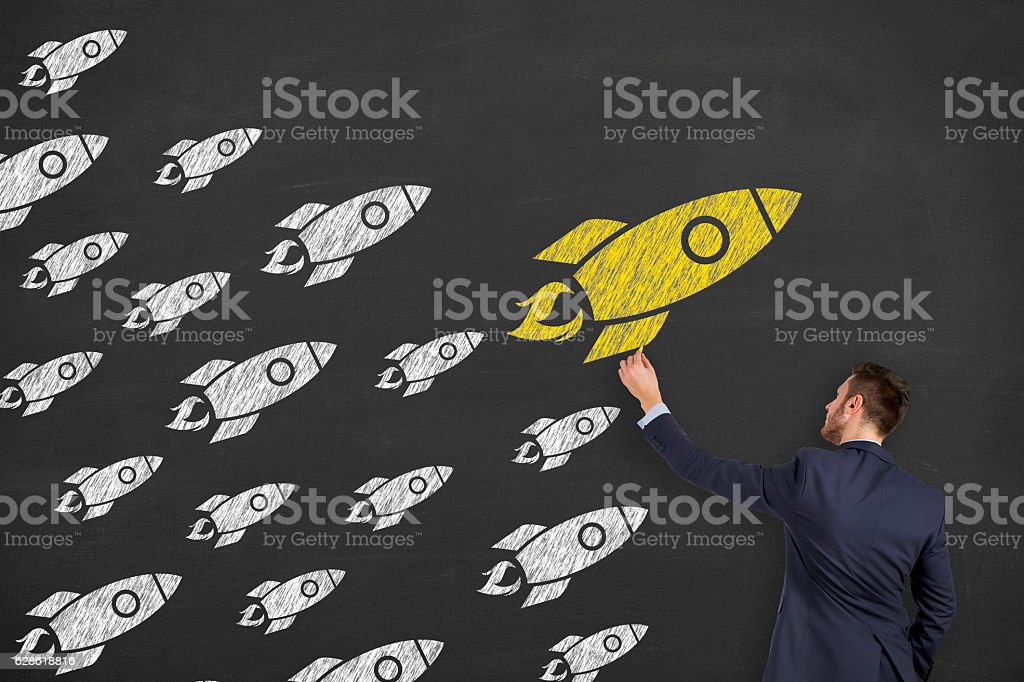 Leadership concept with rocket on chalkboard background stock photo