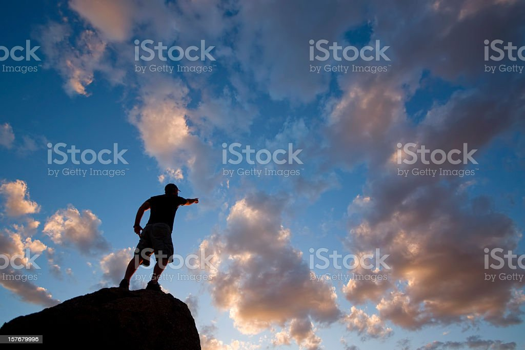 leadership: sunset sky silhouette of man pointing the way stock photo