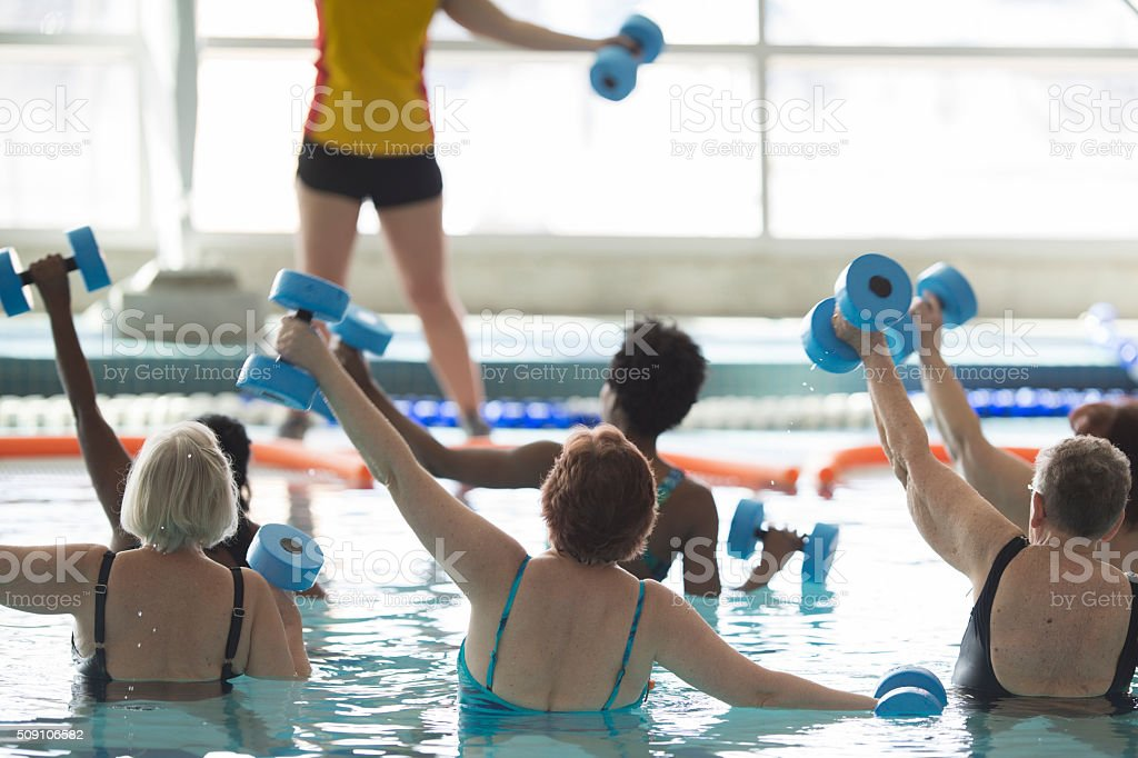 A multi-ethnic group of adults are in the public swimming pool and...