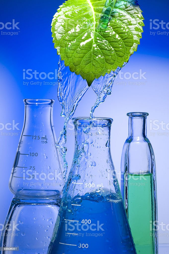 A leaf pouring water into beakers royalty-free stock photo