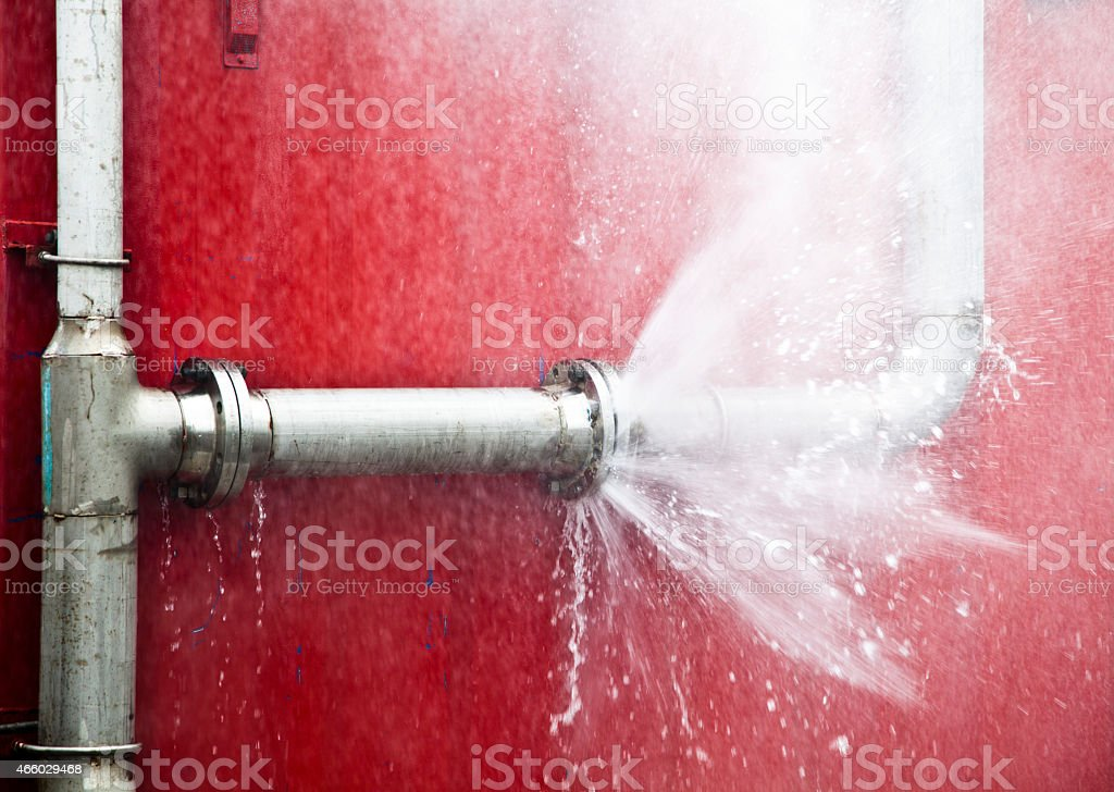 Leaking pipe spraying water onto a red wall stock photo