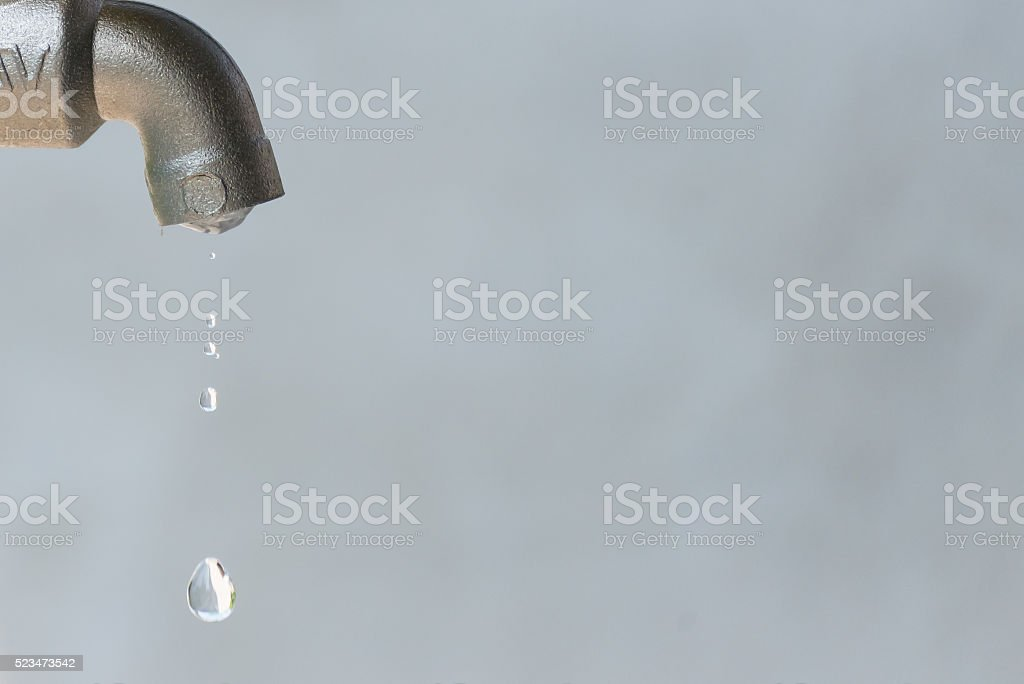 leaking silver faucet with water drop stock photo