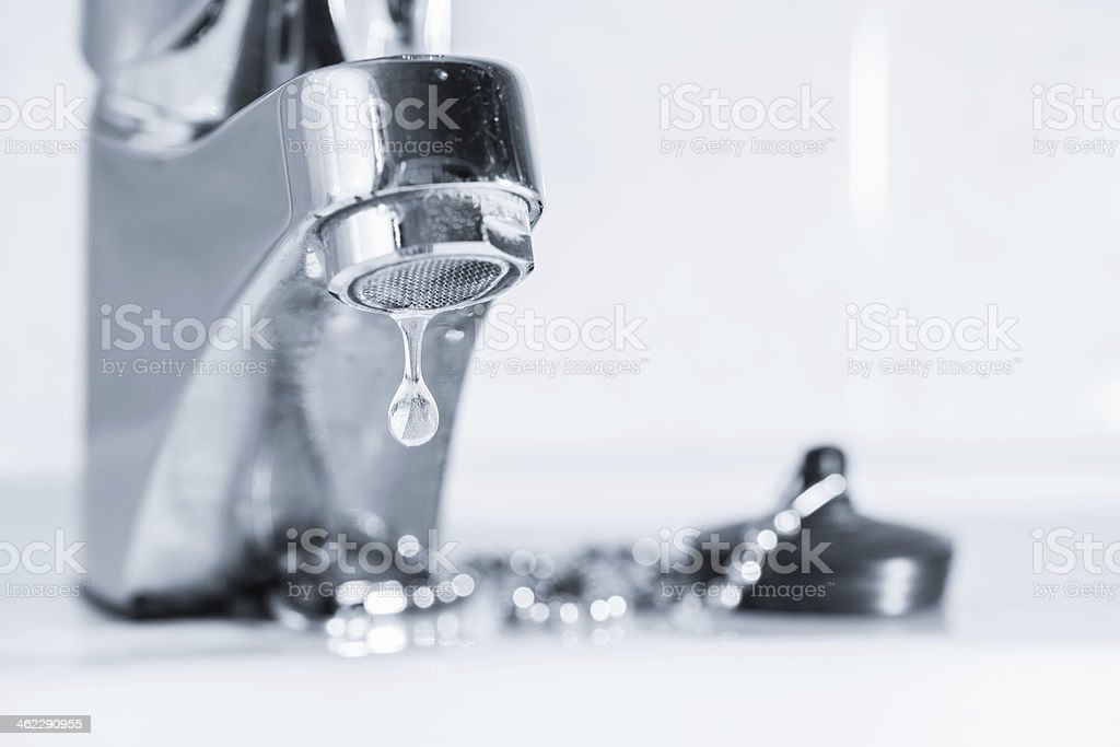 A leaking tap faucet dripping water in a sink stock photo