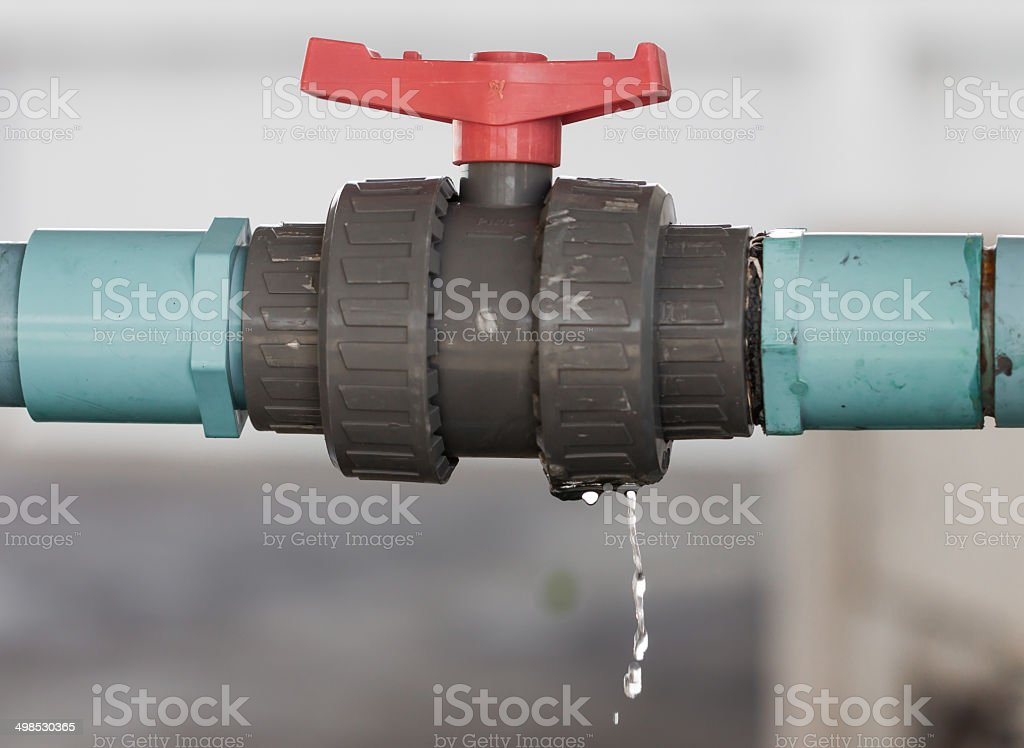 leaking water from blue pipe stock photo