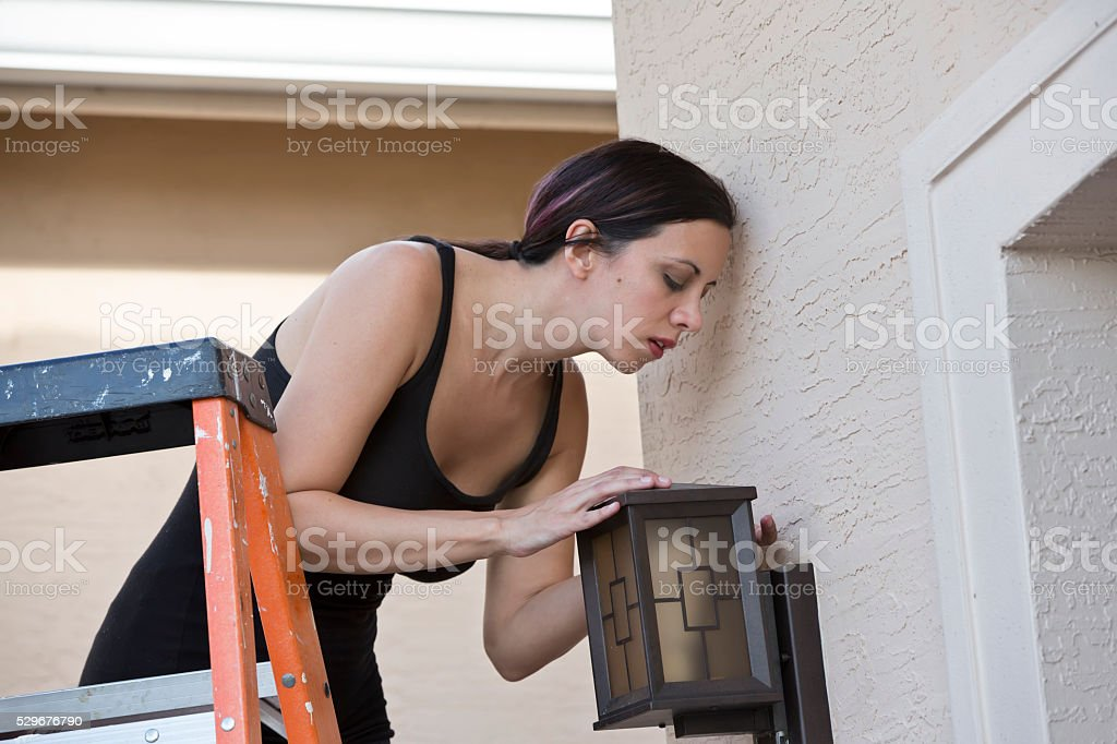 'Lean in'- Real female electrician installing outside lighting stock photo