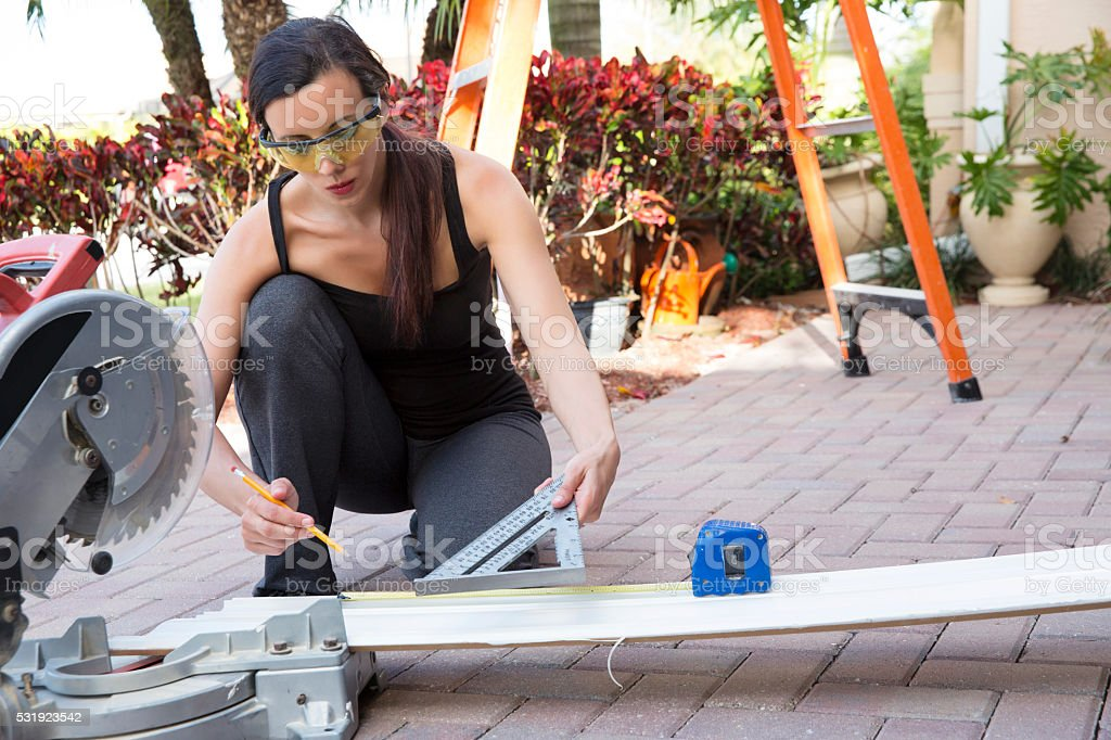 Lean in. Real woman carpenter measuring a wooden board stock photo