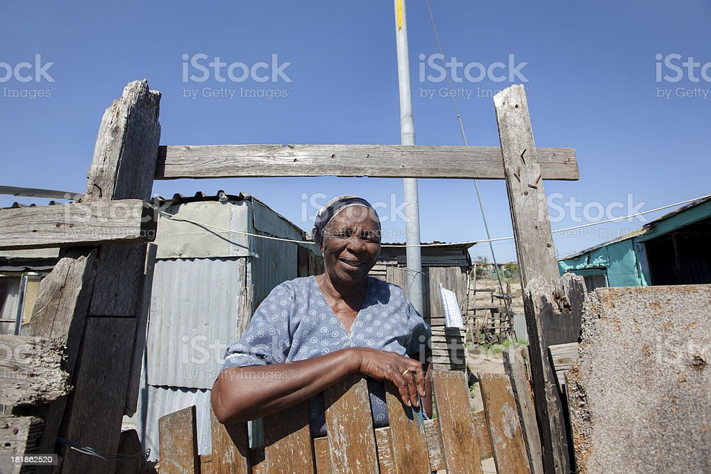 Leaning on Shack Gate, Gugulethu, Cape Town, South Africa. royalty-free stock photo