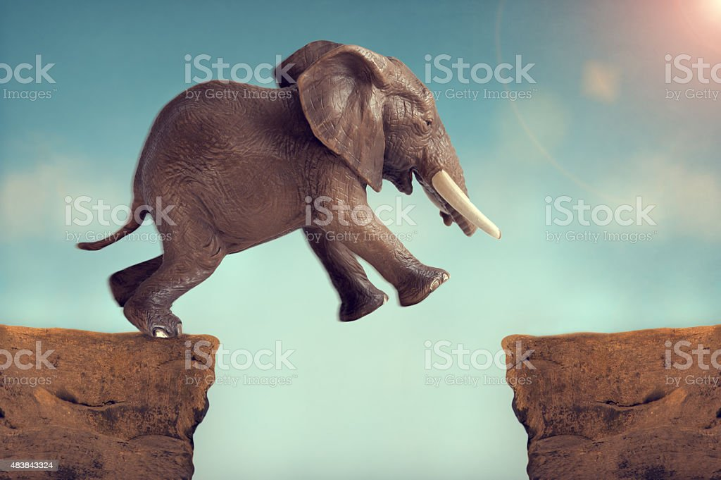 leap of faith concept elephant jumping across a crevasse stock photo