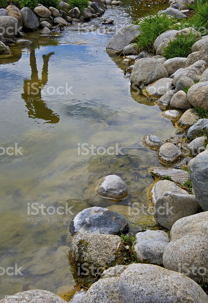 Leap of Faith. Reflection seen as woman jumps over stream. stock photo