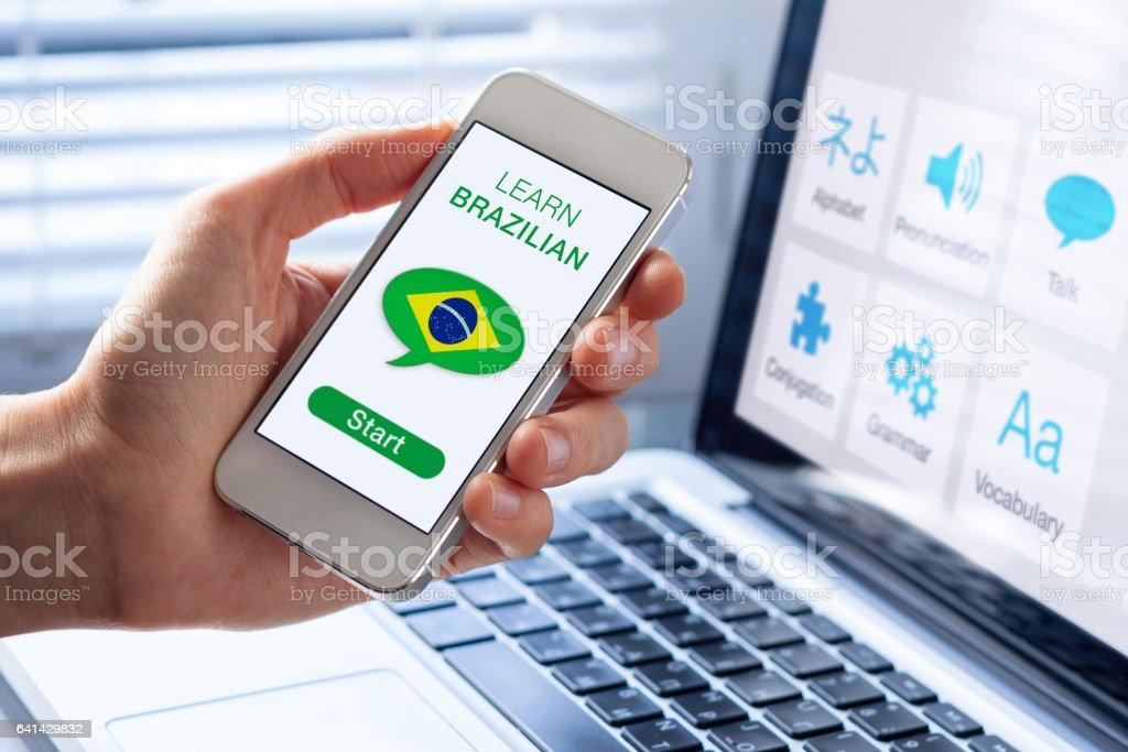 Learn Brazilian Portuguese online concept, mobile phone, flag of Brazil stock photo