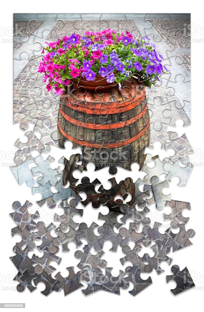 Learn gardening a little by little - Wooden barrel with flowerpot in puzzle shape stock photo