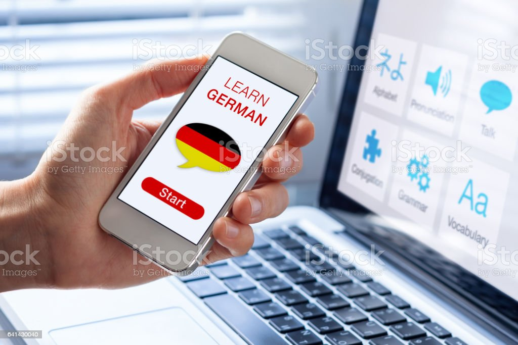 Learn German language online concept, mobile phone, flag of Germany stock photo