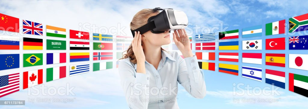 Learn languages in the future technology concept, Woman wearing virtual reality VR glasses. 360 degrees. isolated in blu sky and flags background stock photo
