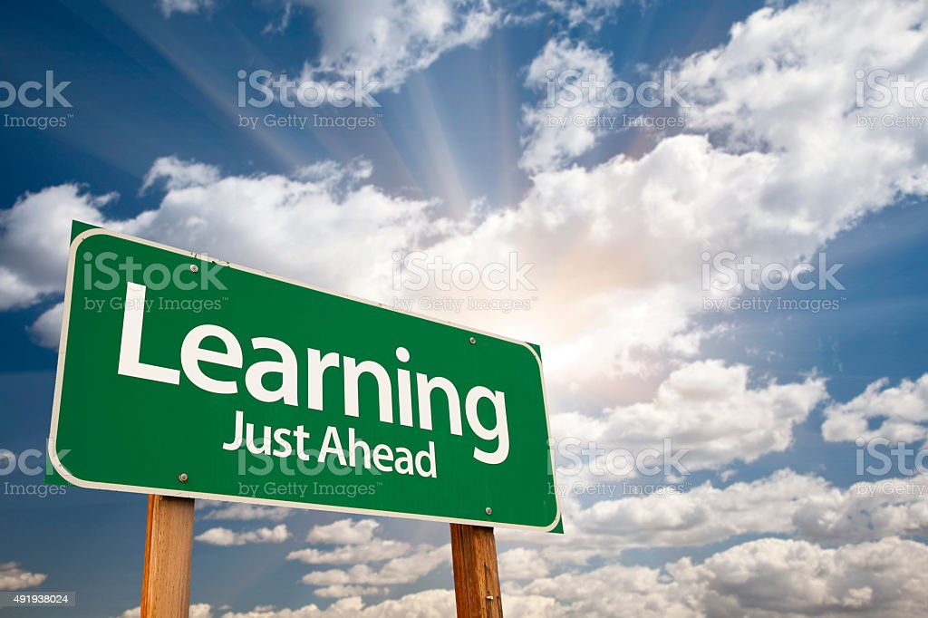Learning Green Road Sign Over Clouds stock photo