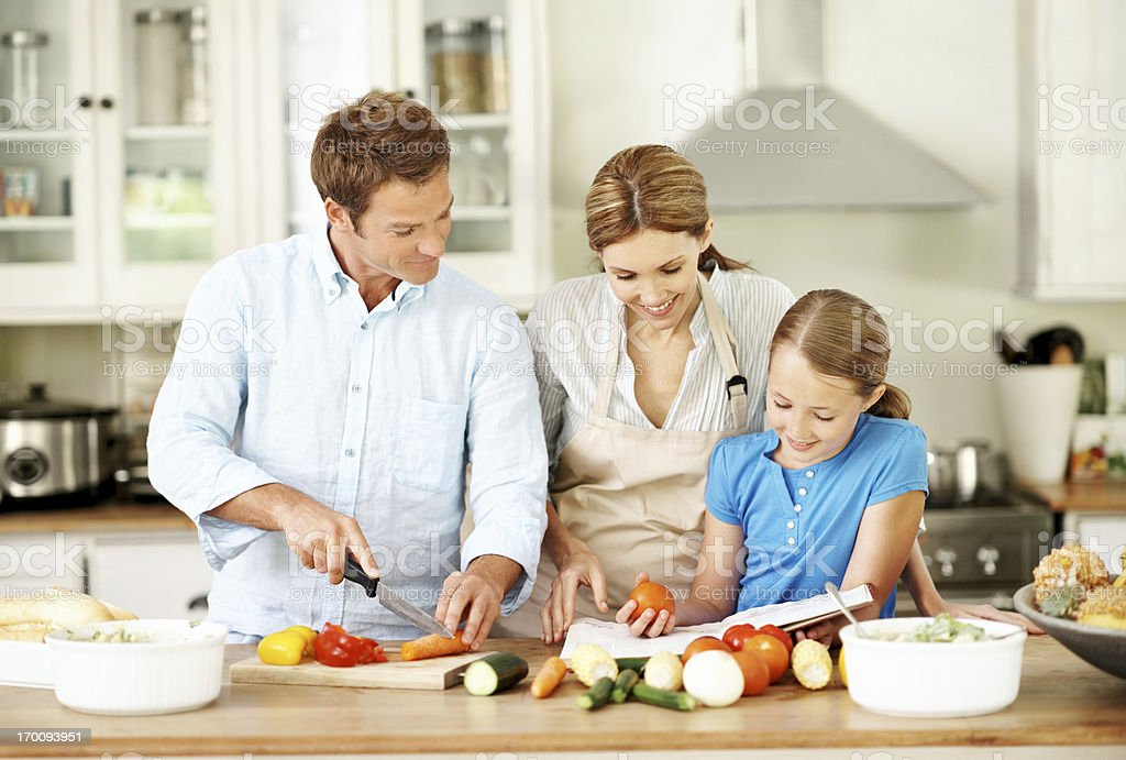 Learning how to cook with mum and dad royalty-free stock photo