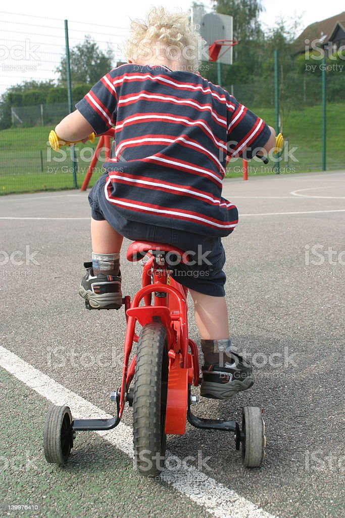 Learning to ride his bicycle with stabilisers stock photo