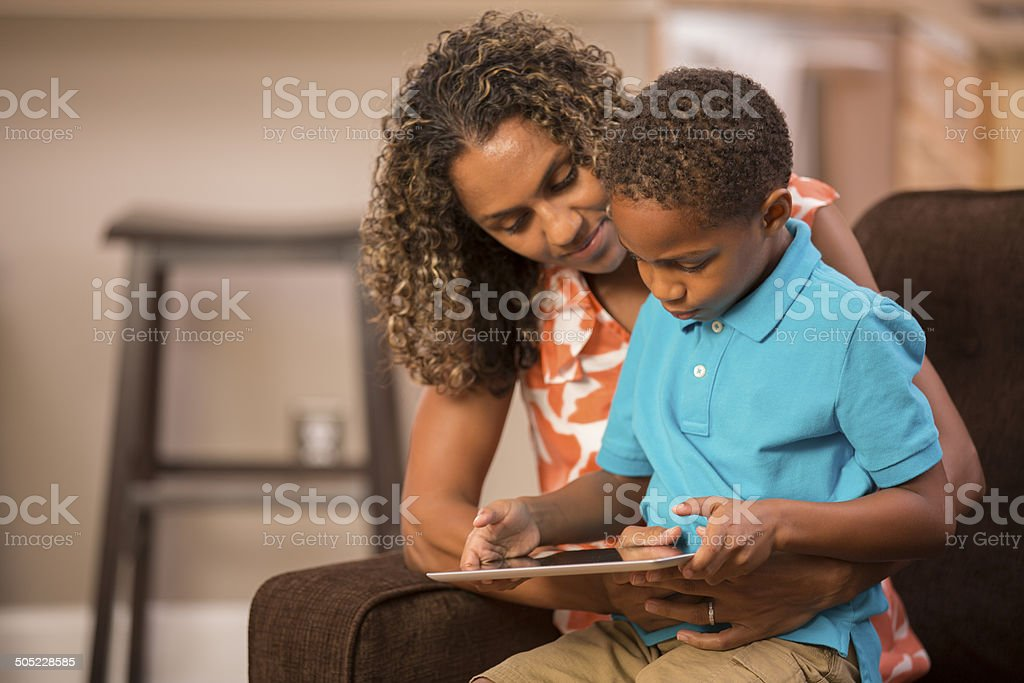 African descent mother teaches her young son at home using digital...