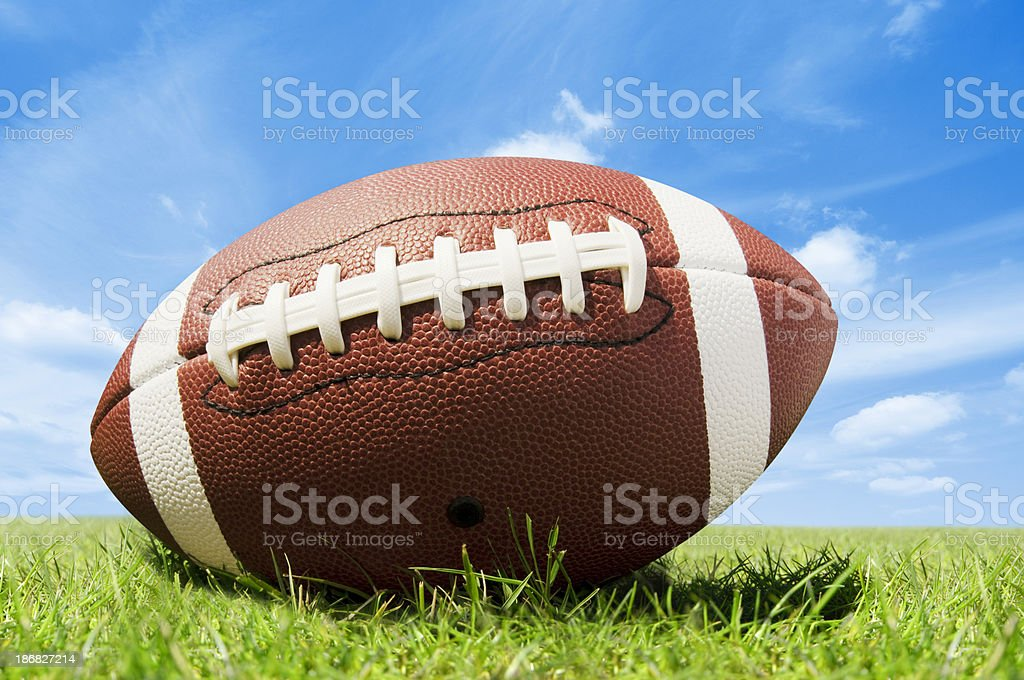 Leather american football on grass pitch with blue sky royalty-free stock photo