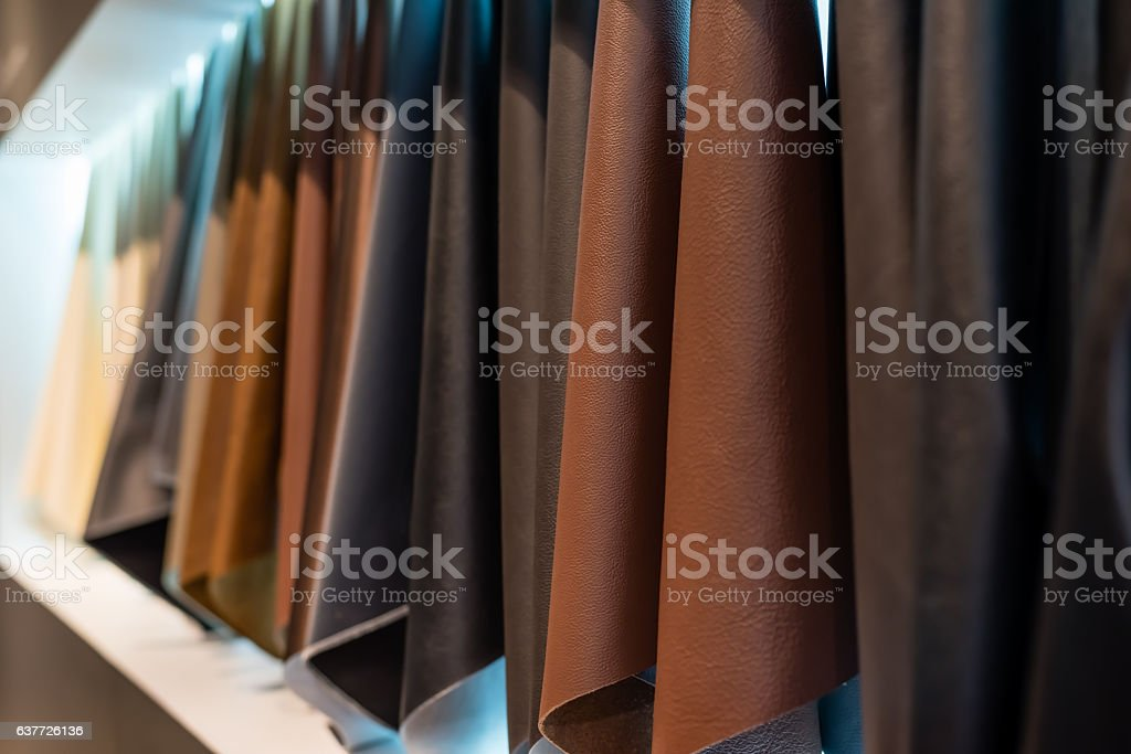 leather and cloth sample hanging on a white wall background stock photo
