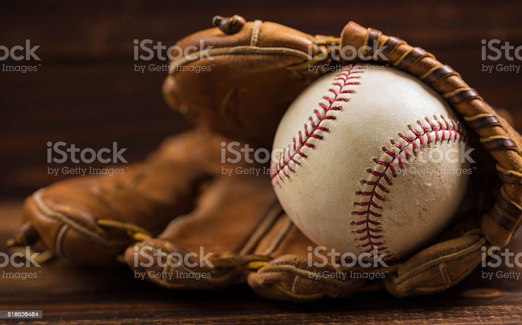 Leather baseball glove and ball on a wooden bench stock photo