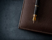 Leather brown notebook with fountain pen.