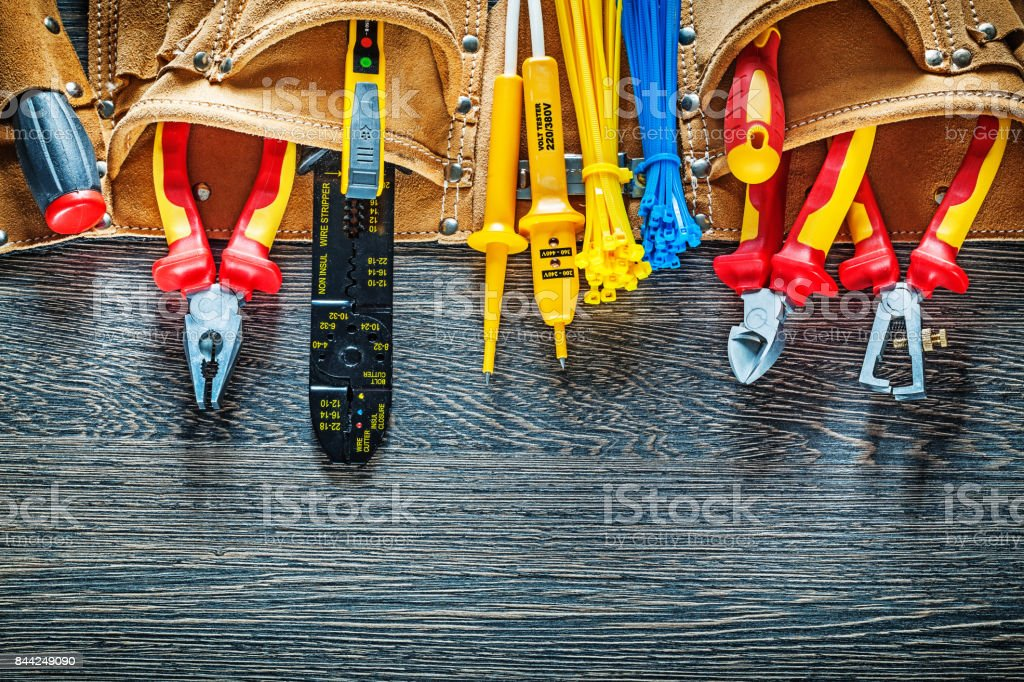 Leather construction belt electric tools on wooden board electri stock photo