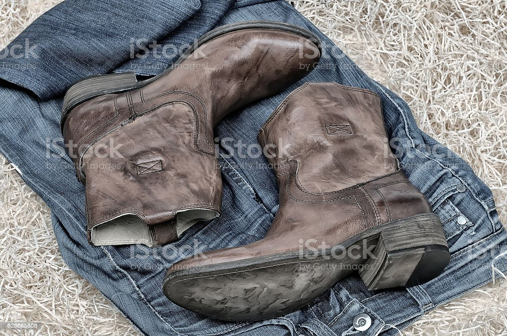 Leather cowboy boots and jeans on straw stock photo