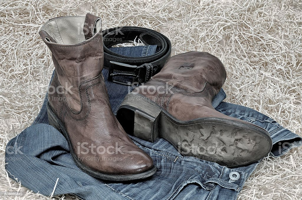 Leather cowboy boots leather belt and jeans on straw stock photo