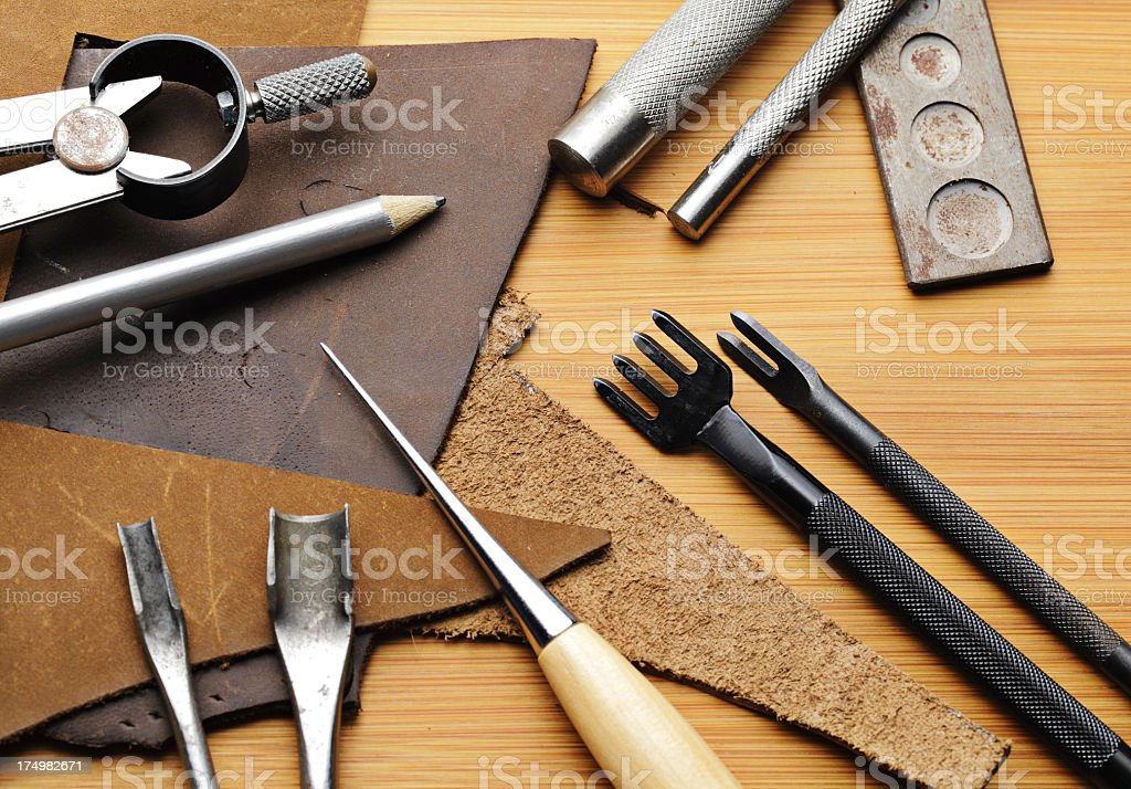 Leather craft equipent on the wooden table stock photo