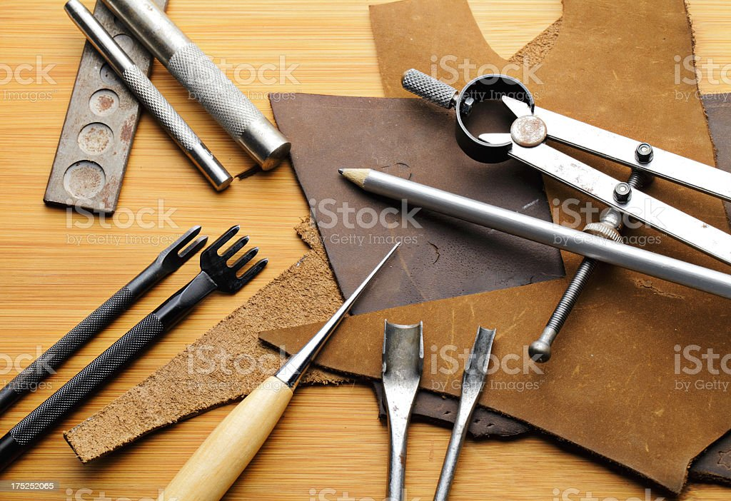 Leather craft equipent on the wooden table with pencil stock photo