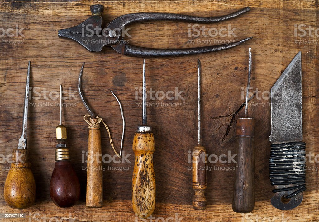 Leather craft tools on a wooden background. Craftmans work desk stock photo