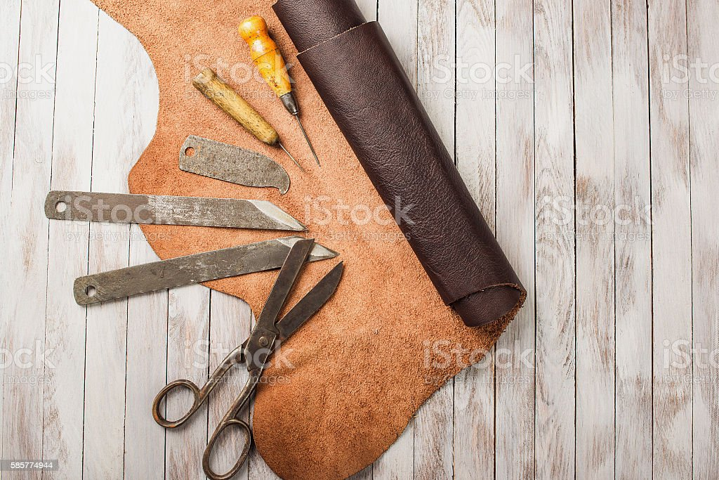 Leather craft  work place.Tools on the wooden background. stock photo