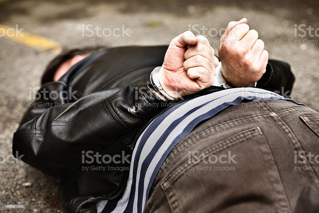 'Leather jacketed man, handcuffed, lies in road' stock photo